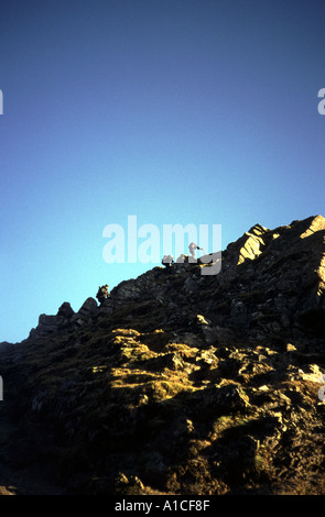 Walker climbing to the top of Ben Lomond - Stock Photo