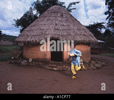 Young boy running past mud hut with bread - Stock Photo