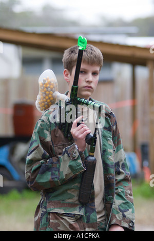 Teenage youth takes a break between rounds in a paintball game - Stock Photo