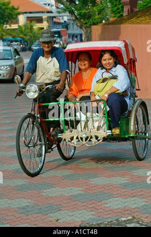 Rickshaw with two women passengers on road near Dutch Square Melaka - Stock Photo