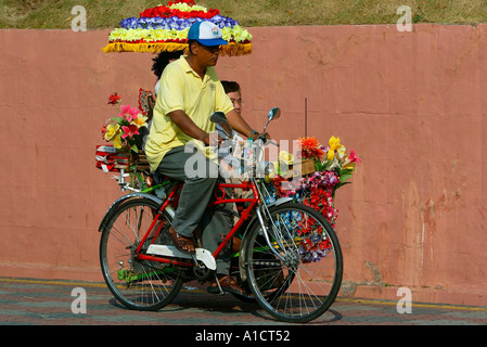 Tourist bicycle rickshaw with visitor on road near Dutch Square Melaka - Stock Photo
