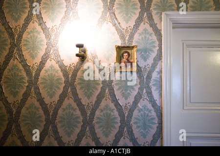 Bright lamp glowing next to a small framed baroque painting hung on a wall with floral pattern near the door - Stock Photo