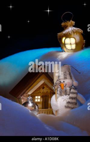 Wonderful Christmas Still Life Snowman near his cottage house christmas decorations - Stock Photo