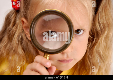 Little girl with a magnifying glass - Stock Photo
