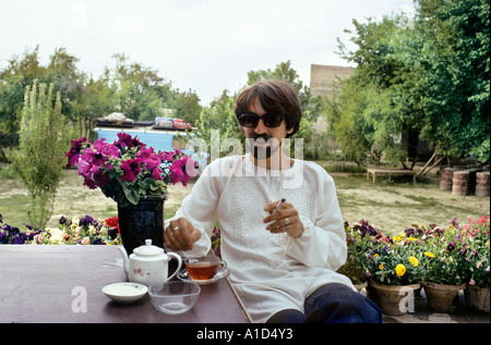 tourist in courtyard of hotel garden drinking tea and smoking beard sunglasses flower pot table cloth traveller - Stock Photo
