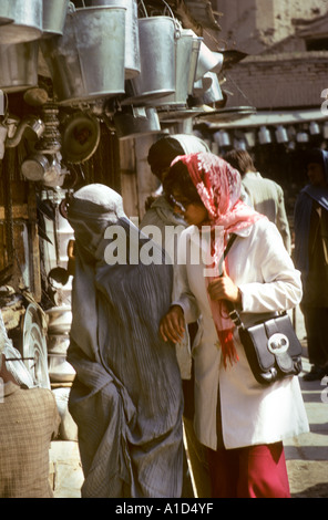 two women one in burka western clothes handbag and headscarf shop shopper shopping buy buying walk window street - Stock Photo