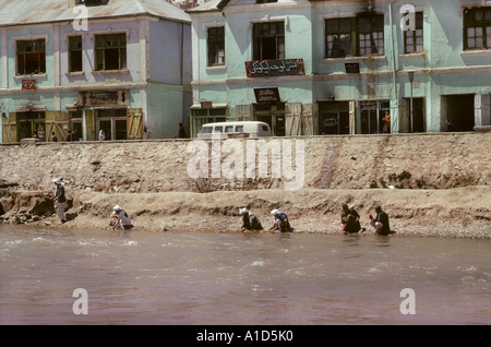 Kabul City River in full flow with people doing their daily ablutions Afghanistan Asia men sit sat squat - Stock Photo