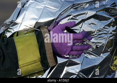 An EMT has his hand on patient under a silver emergency blanket at a mass casualty incident - Stock Photo