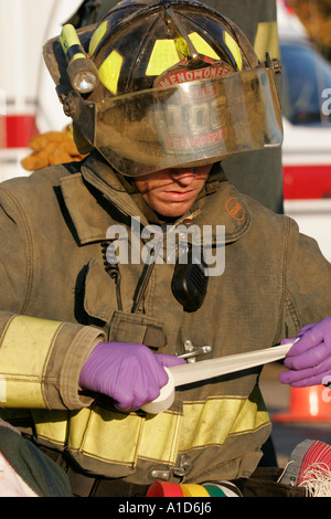 A fire fighter ripping off medical tape to put onto a patient at an emergency scene - Stock Photo