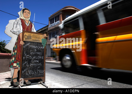 A yellow bus passes a restaurant menu board in Mosta, Malta. - Stock Photo