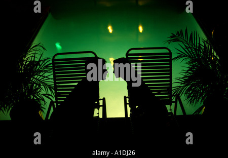 Late in the evening two honeymooners kiss at a resort hotel s swimming pool Stock Photo