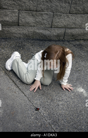 Girl sits on concrete floor watching butterfly at Butterfly House at Pacific Science Center at Seattle Center Seattle - Stock Photo