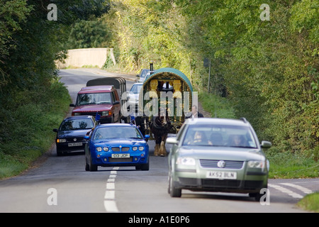 Cars overtake shire horse drawn gypsy caravan on country lanes Stow On The Wold Gloucestershire United Kingdom - Stock Photo