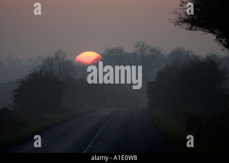 Winter sun sets over empty country road Swinbrook Oxfordshire UK - Stock Photo
