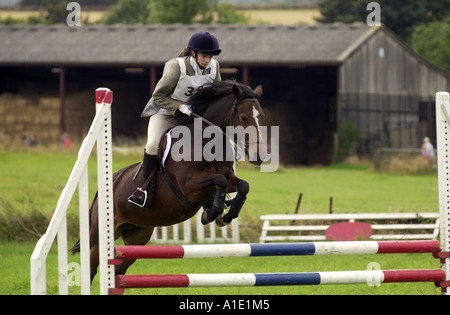 Young woman rides bay pony over showjump at horse trials eventing competition Gloucestershire United Kingdom - Stock Photo
