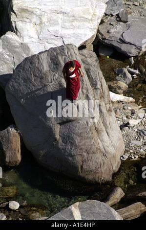 One lone tibetan buddhist man monk in traditional dress walking searching way through mountain gorge - Stock Photo