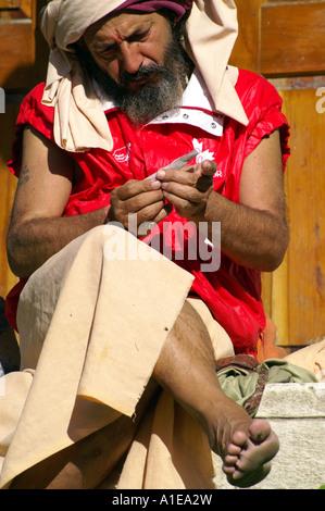 Holy indian old man rolling hashish joint cigarette, sitting outdoors bare feet in jacket vest, Vashisht, India - Stock Photo