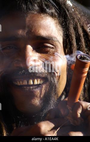 Face portrait smiling sadhu indian man with hashish pipe smoking and dreadlock hair, Vashisht, India - Stock Photo