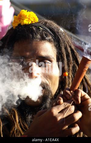 Face portrait smiling sadhu indian man with hashish pipe smoking and dreadlock hair, Vashist, India - Stock Photo