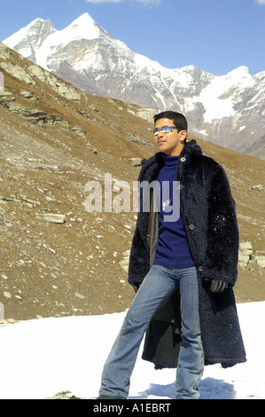 Handsome indian man in black fur coat posing on white snow in in Rohtang Pass, Indian Himalaya - Stock Photo