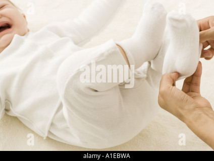 Baby being dressed - Stock Photo