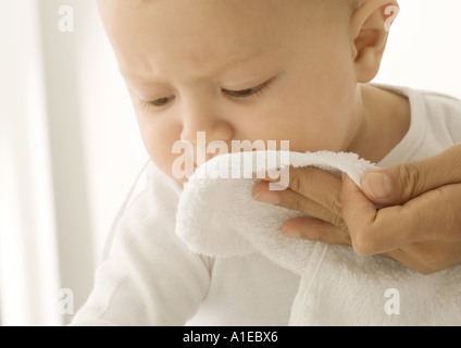 Baby having face wiped - Stock Photo
