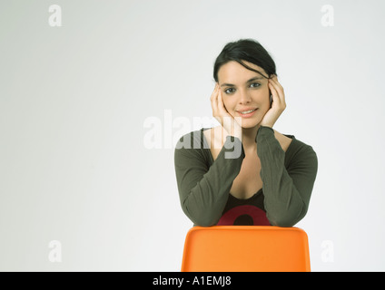 Young woman sitting backwards on chair, smiling - Stock Photo