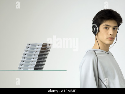 Young man listening to headphones, next to stack of cds - Stock Photo