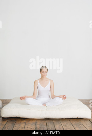Young woman sitting in lotus position on futon mattress