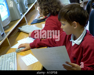 Junior schoolboy working on his computer terminal in school computer classroom - Stock Photo