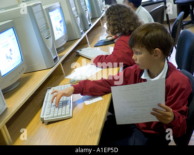 Junior schoolboy works on his computer terminal in school computer classroom - Stock Photo
