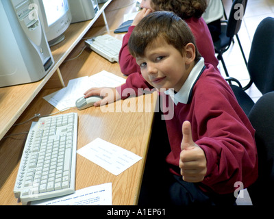 Confident junior schoolboy gives the thumbs up sign to camera in school computer classroom - Stock Photo