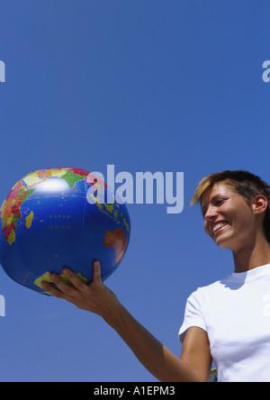 Young woman holding globe ball - Stock Photo