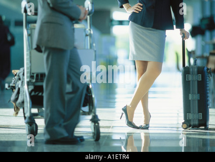Businessman and businesswoman standing with luggage in airport - Stock Photo