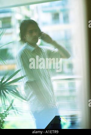 Reflection of man using phone - Stock Photo