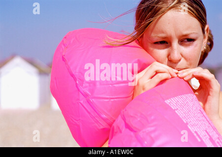 Girl blowing an inflatable lifebelt - Stock Photo