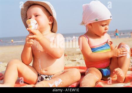 Toddlers having ice cream on the beach - Stock Photo
