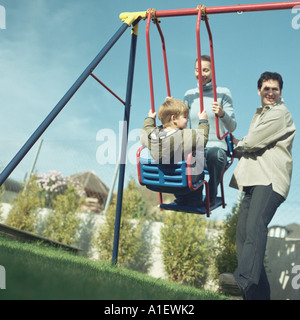 Man pushing wife and son on swing - Stock Photo