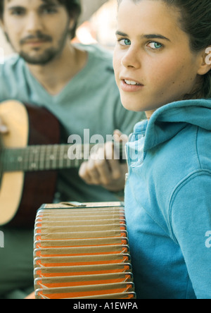 Young woman playing accordian and young man playing guitar - Stock Photo