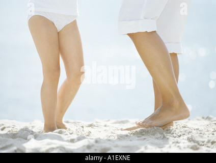 Mother and daughter standing on sand, low section - Stock Photo