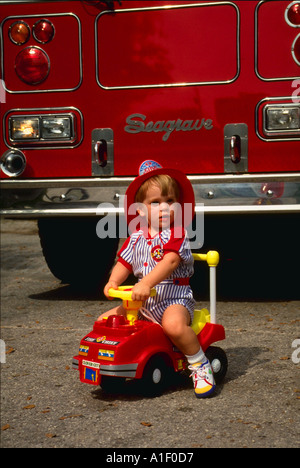 Two year old boy wearing fire hat and riding toy fire truck in front of real fire truck - Stock Photo