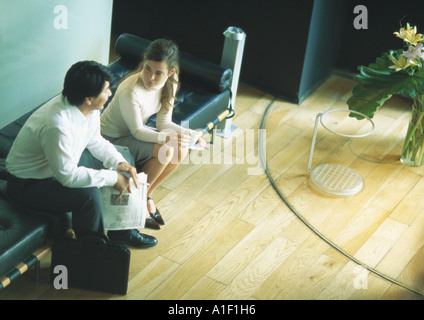 Man and woman sitting on bench in lobby, high angle view - Stock Photo