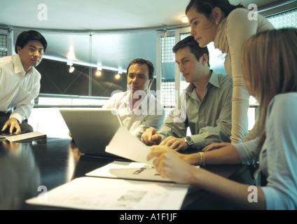 Businesspeople working around laptop