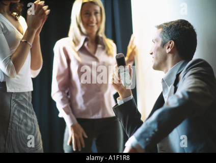 Businessman holding up cellphone, female colleagues smiling and clapping - Stock Photo