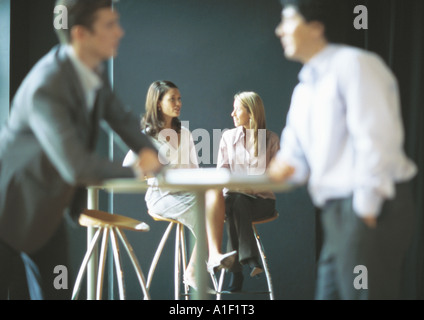 Businesspeople talking in cafe setting - Stock Photo