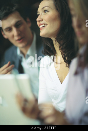 Businesswoman smiling between two co-workers - Stock Photo