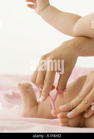Baby having toenails cut, cropped view - Stock Photo