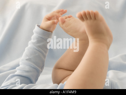 Baby touching toes, cropped view - Stock Photo