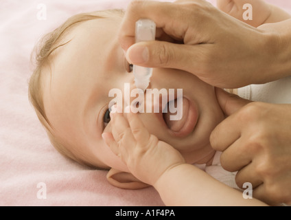 Baby having nose cleaned - Stock Photo