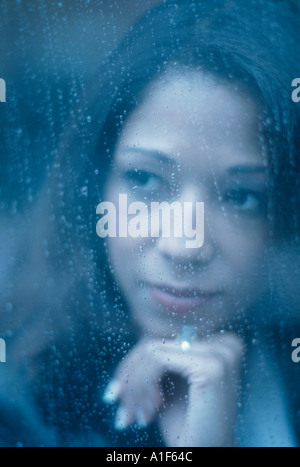 Moody portrait of African American woman looking through window on rainy day - Stock Photo